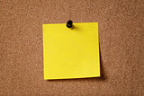 yellow reminder sticky note on cork board