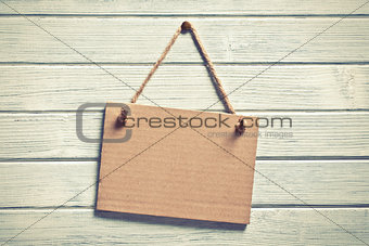 paper board hanging on wooden wall