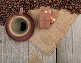 Coffee cup and chocolate on wooden table