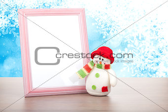Blank photo frame and christmas snowman on wooden table