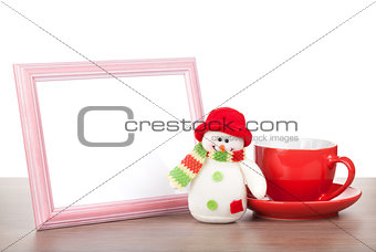 Blank photo frame, christmas snowman and coffee cup on wooden ta