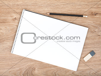Blank notepad, pencil and eraser on the wooden table