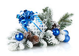 Gift box and christmas decor on snowy fir tree