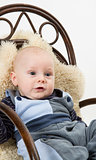 newborn child in chair with sheepskin
