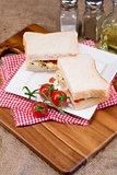 Fresh egg and tomato on white sandwich in rustic kitchen setting
