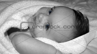 Beautiful baby in a towel with blue eyes