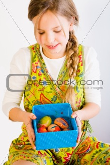Young girl looking at a box with easter eggs