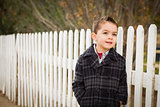 Young Mixed Race Boy Waiting For Schoold Bus Along Fence Outside