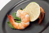 Shrimp with lime on black plate