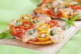 Mini pizzas with mozzarella, cherry tomatoes and basil