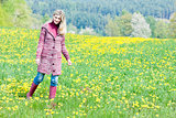 woman wearing rubber boots standing on spring meadow