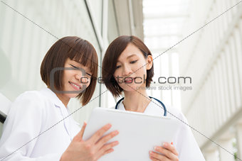 Asian doctors having discussion with digital pc tablet