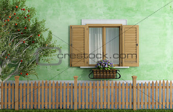 Old house with wooden fence and apple tree