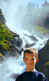 Portrait boy on summer waterfall background