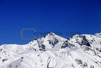 Winter snowy mountains and blue clear sky