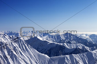 Snowy rocks and blue sky in nice sun day, view from off piste sl