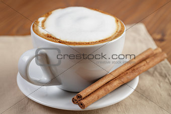 cup of fresh hot cappuccino with cinnamon sticks