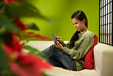 Asian girl with touch pad relaxing on sofa at home