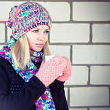 Young Woman with coffee cup Winter time wearing knitted sweater, hat and scarf with mittens Lifestyle concept trendy colors with white brick wall on background