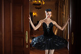 Ballerina in black tutu standing in doorway