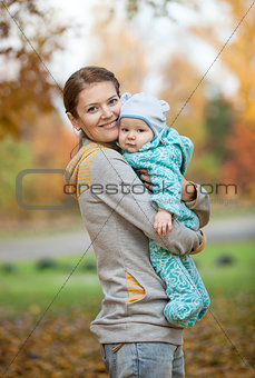 Portrait of young woman and her baby son in autumn park