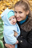 Young woman with baby in autumn park
