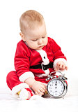 Cute little boy in Santa costume playing with alarm clock saying 12 p.m.