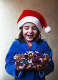girl in wearinlg santa hat holds a dish with chocolates