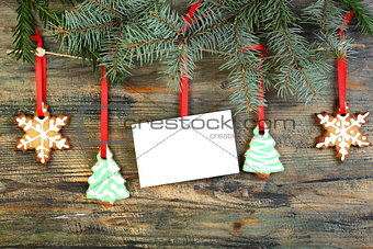 Card and Christmas cookies on fir branches.