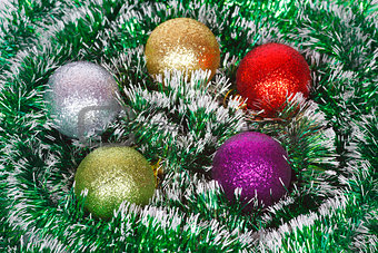 Five Christmas colored balls on the green tinsel