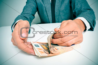man in suit counting euro bills