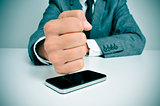 businessman hitting a smartphone with his fist