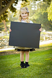 Cute Little Blonde Girl Holding a Black Chalkboard Outdoors