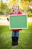 Cute Girl Holding a Green Chalkboard Wearing Winter Coat Outdoor