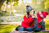 Little Girl with Baby Brother Wearing Coats and Hats Outdoors