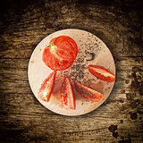 Sliced tomato on wooden plate