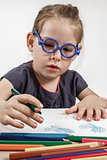 Cute Little Girl with Blue Glasses Painting on a School Desk
