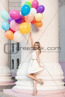 beautiful lady in retro outfit holding a bunch of balloons on th