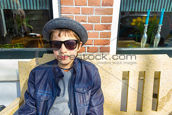 Boy with glasses sitting on a bench in front of the house, The N