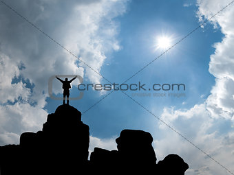 Happy man standing at mountain top