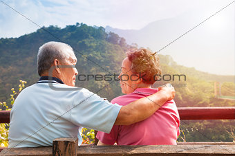 senior couple sitting on bench in nature park