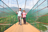 happy senior couple walking on bridge in nature park