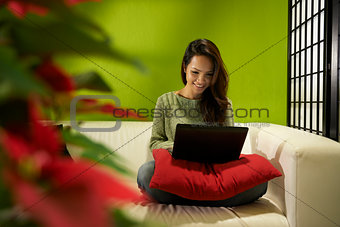 Asian girl with computer sitting on sofa at home