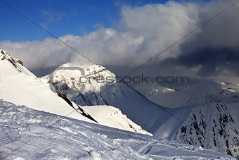 Off-piste slope and sunlit mountains in clouds