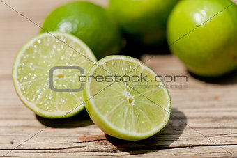 green fresh lime on wooden table macro closeup outdoor