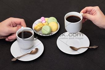 Couple drinking coffee with macaroon