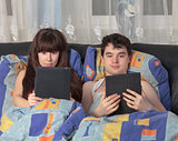 Young couple using tablet PC in their bed