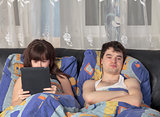 Young couple with tablet PC in their bed