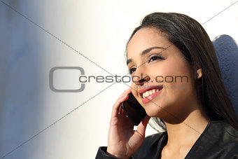Beautiful woman talking happy on the mobile phone in a sunny day