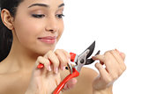 Humorous beautiful woman making manicure with a secateurs